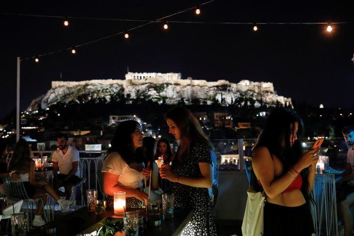 Bezoekers van een bar in Athene, met op de achtergrond de Akropolis.