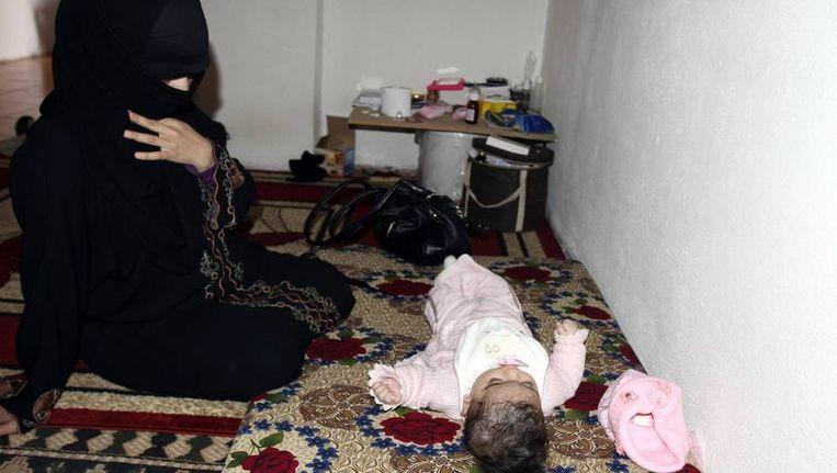 Een vluchteling uit Syrië zit bij haar baby in Libanon. Beeld reuters