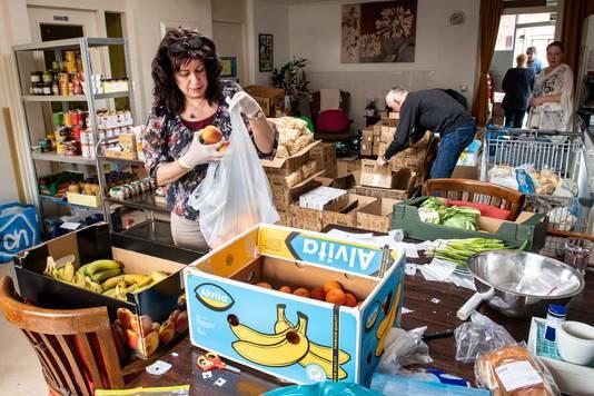 Vrijwilligers van Vincentius stellen in het verenigingsgebouw aan de Horstacker pakketten met boodschapen samen.