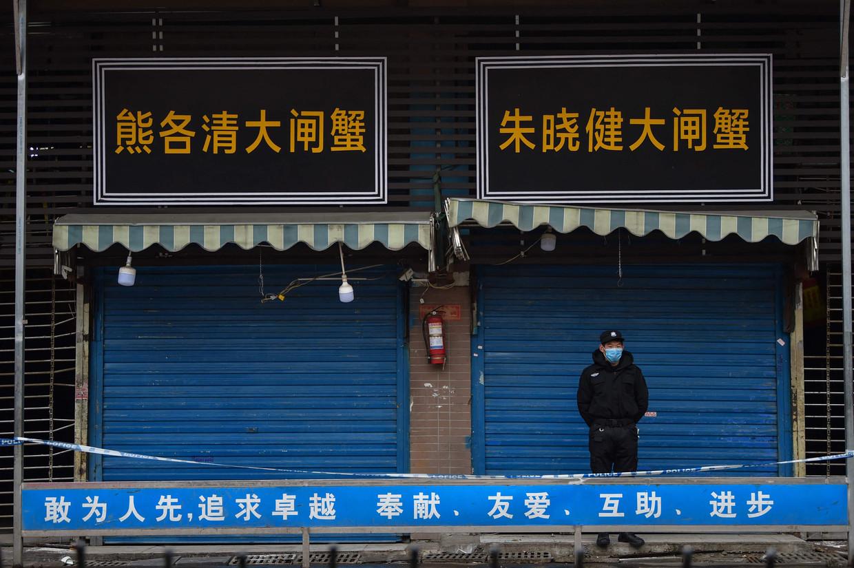 Een bewaker bij de markt waar het coronavirus werd ontdekt. Beeld AFP