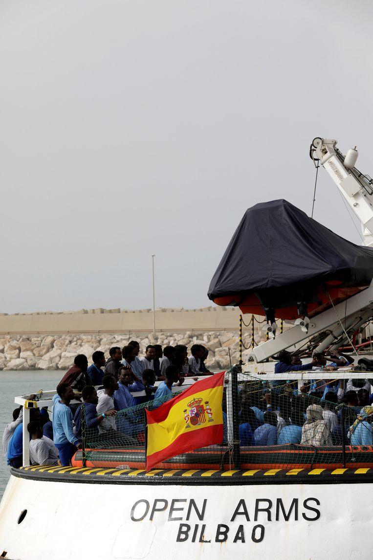 Migranten wachten tot ze van de reddingsboot van Open Arms af mogen in de haven van Pozzalo in Italië. Beeld REUTERS
