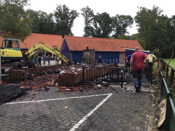 Ouders kwamen zaterdagmorgen direct helpen om de ravage na de brand in de opslagloods voor oud paper bij basisschool Honesch op te ruimen.