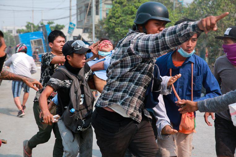 Een man met een hoofdwond wordt weggedragen in Mandalay, Myanmar. Het leger schiet gericht op demonstranten tegen de militaire coup. Beeld AP