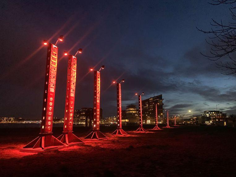 De staanders zijn bekroond door lampen die met wisselende kleuren de nachtelijke steiger het aanzicht geven van een ufolandingsbaan. Beeld