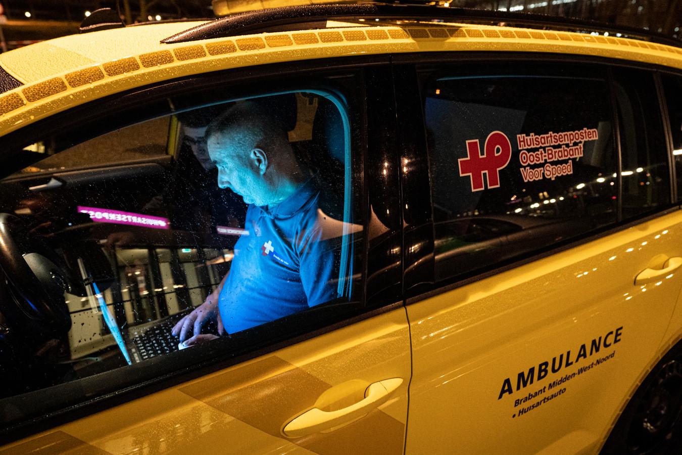 Nederland,  Den Bosch, ambulancewagen van huisposten Oostbrabant voor spoed zit te computeren voor het ziekenhuis