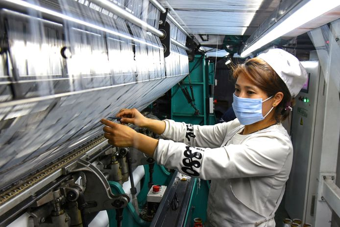 Een Chinese arbeidster aan het werk in een textielfabriek in Lianyungang.