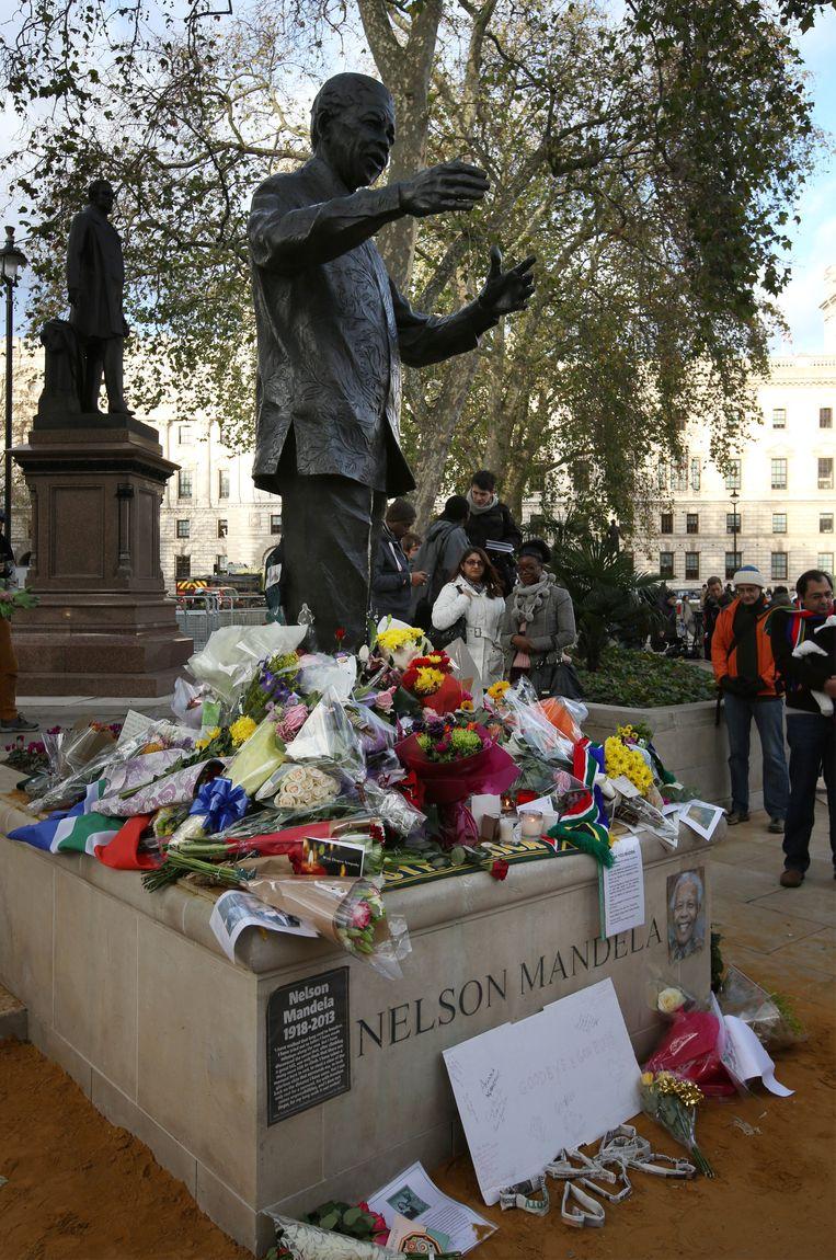 Bloemen aan het standbeeld van Mandela in Londen, na zijn overlijden.  Beeld Getty Images