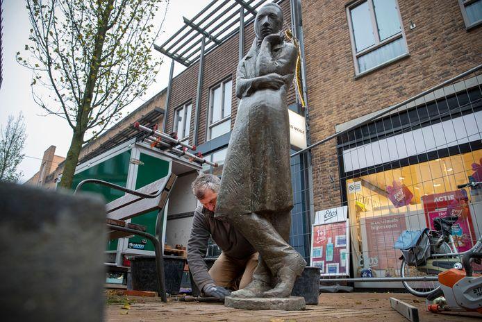 Han van Ee verricht de laatste werkzaamheden voor het beeld van Heinrich Heine, gemaakt door Waldemar Otto, op de Grotestraat
