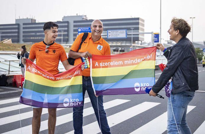 Presentator Klaas van Kruistum overhandigt een voetbalfan een regenboogvlag.