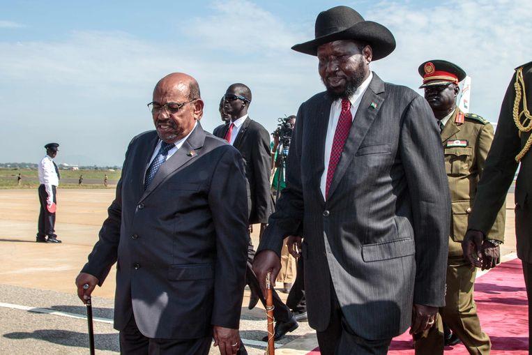 De Soedanese president, Omar al-Bashir (links) en de president van Zuid-Soedan, Salva Kiir, lopen samen over een rode loper op de landingsbaan na Bashirs aankomst op het Juba International Airport in Zuid-Soedan.  Beeld AFP