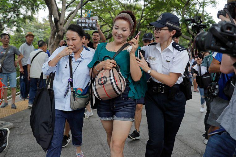 Een Chinese straatartiest wordt begeleid door politie bij het verlaten van het Tuen Mun Park nadat demonstranten haar in het nauw hadden gedreven.  Beeld AP