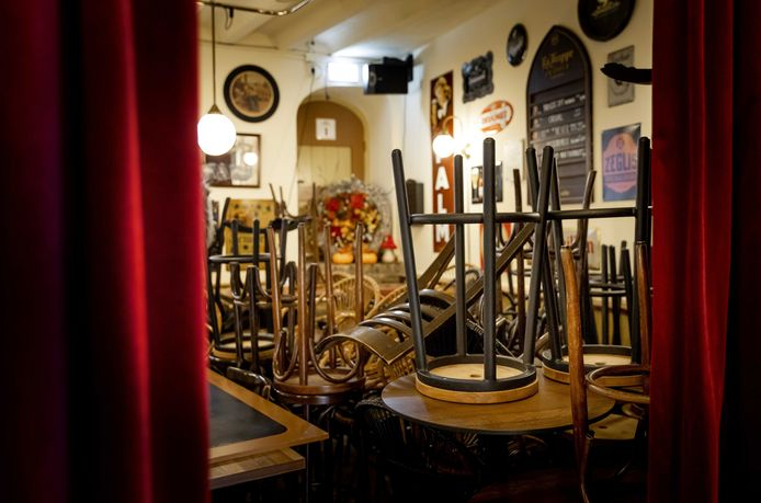 Opgestapelde stoelen in een café, dat gesloten moest blijven.