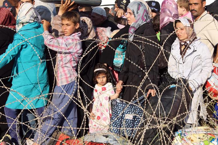 Syrische vluchtelingen in de rij bij de grens van Turkije.