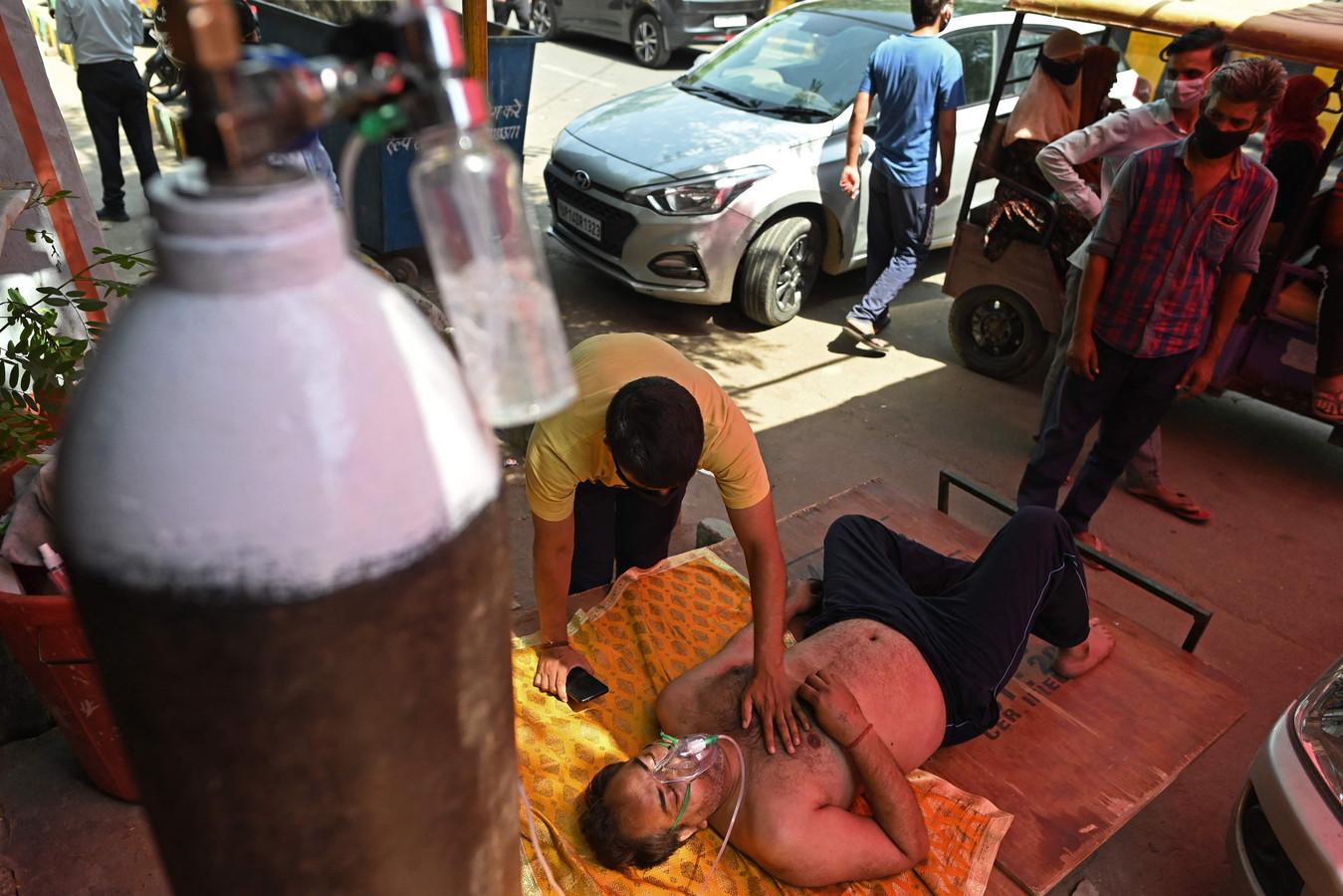 Coronapatiënt wordt langs de kant van de weg geholpen in Ghaziabad, India.