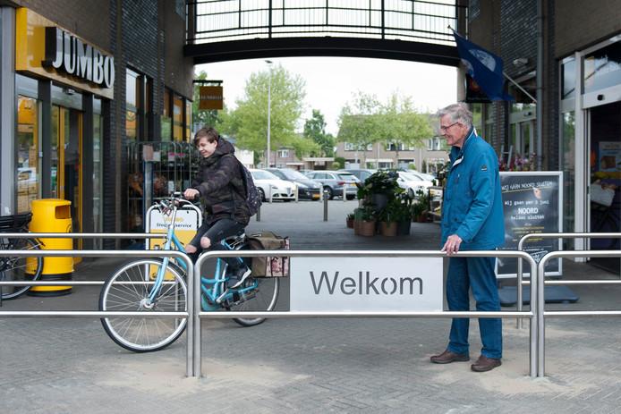Wim de Hair (GemeenteBelangen) kijkt toe hoe bij het winkelcentrum in Raalte-Noord een fietser tussen de hekken door slalomt.