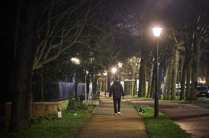 Een man laat zijn hond uit in Den Haag. Het demissionair kabinet overweegt de invoering van een avondklok om de opmars van de Britse variant van het coronavirus een halt toe te roepen.