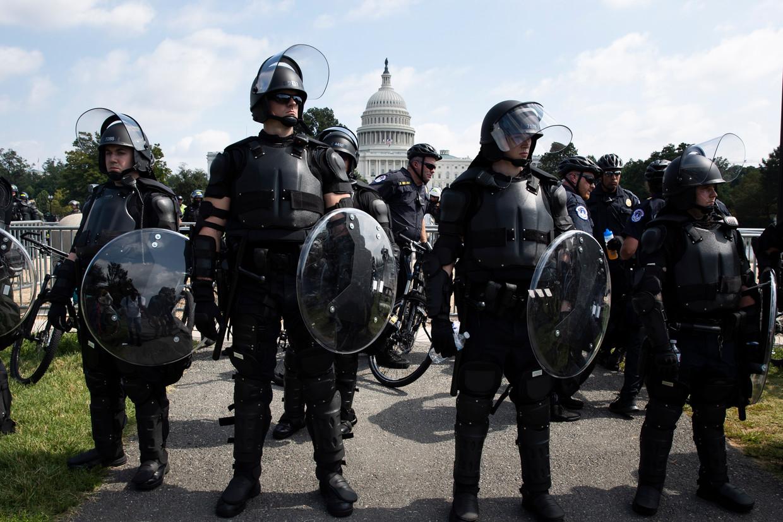 Politieagenten met schilden staan klaar bij het Capitool, waar een paar honderd Trump-demonstranten komen opdagen. Beeld EPA