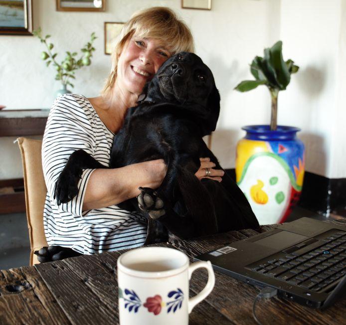 Tijdens het digitale ochtendoverleg kruipt labrador Izzy, van onder de tafel, langzaam op schoot bij Marja Klein Obbink. Beetje voor beetje, alsof het dan minder opvalt.  Meestal draait ze zich op haar rug en gaat dan ongegeneerd, compleet relaxt, met d'r poten wijd voor het beeldscherm zitten.