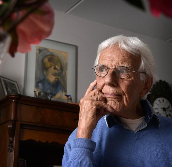 Hans Bots met op de achtergrond het door zijn vrouw geschilderde portret van hun overleden zoontje.