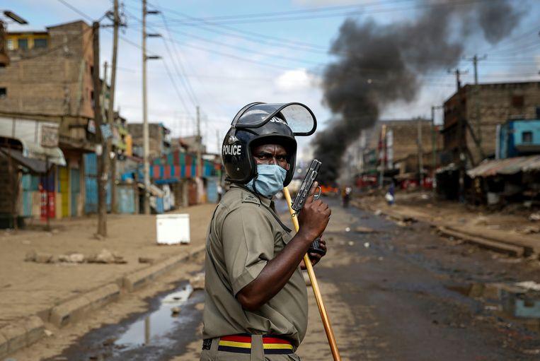 Een politieagent tijdens rellen in de wijk Kariobangi in Nairobi. De regering verordende ontruiming van de wijk, waardoor vijfduizend arme Kenianen dakloos werden midden in de lockdown.  Beeld AP