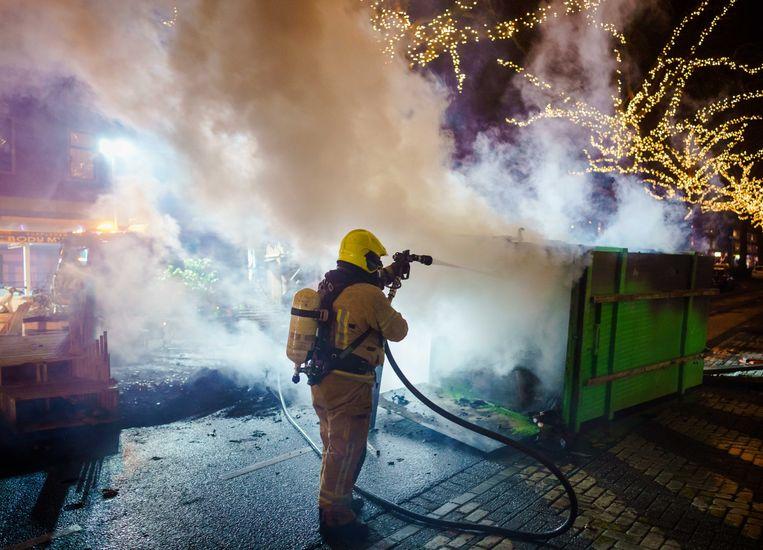 De brandweer blust een brand op de Groene Hilledijk na afloop van de rellen in Rotterdam.  Beeld ANP