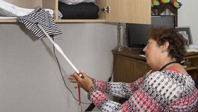 Een bewoonster van Nolenshaghe gebruikt een hulpmiddel om zelf een truitje uit de kast te pakken.