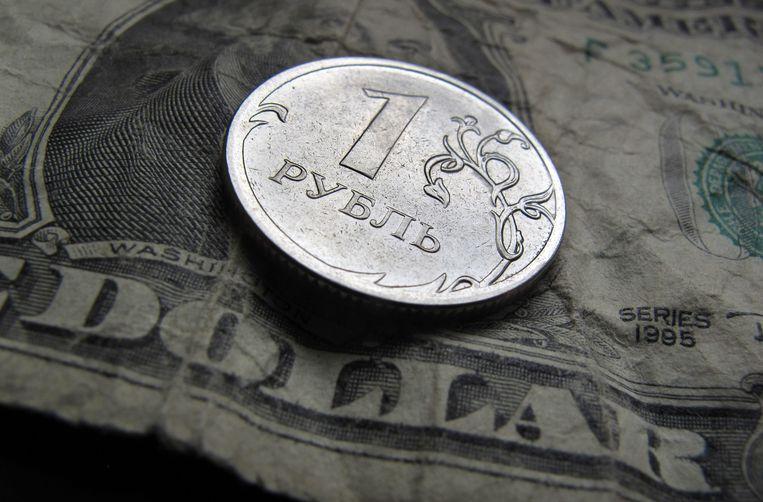 Een munt van 1 roebel bovenop een briefje van 1 dollar Beeld EPA
