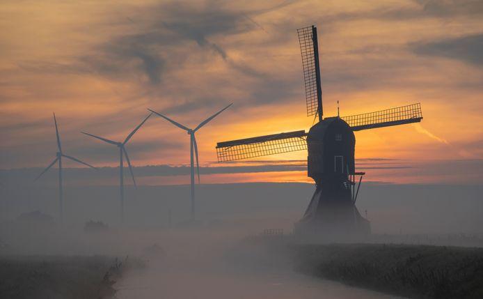 De historische Achterste Molen van Hellouw in de mist, met op de achtergrond de windturbines van Windpark Deil.