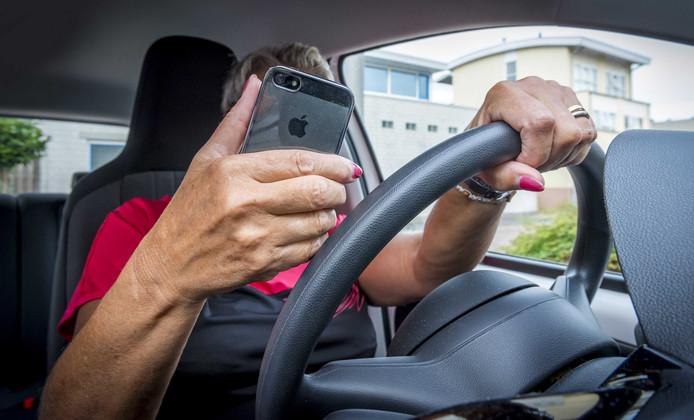 Een automobilist neemt al append deel aan het verkeer.