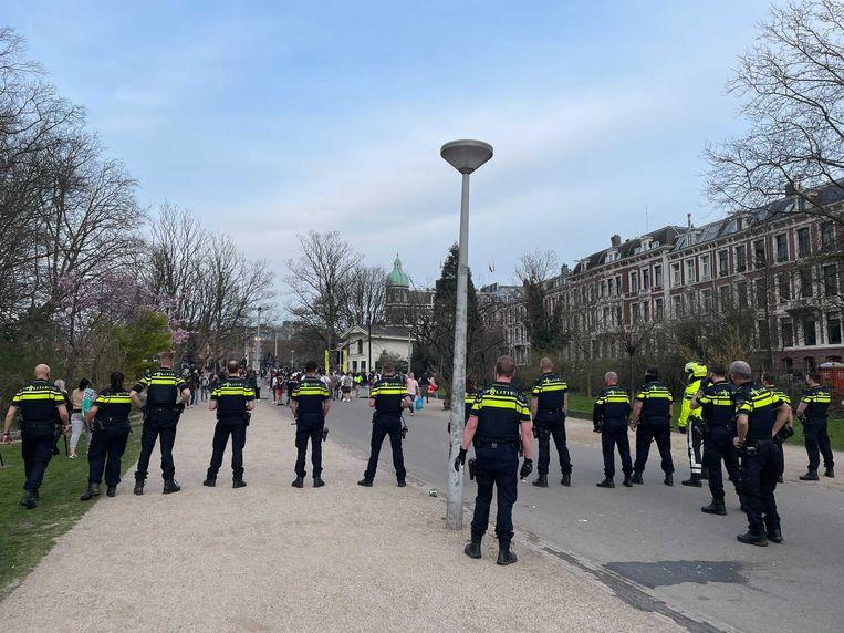 De politie staat in linie in het inmiddels grotendeels ontruimde Vondelpark. Beeld Het Parool