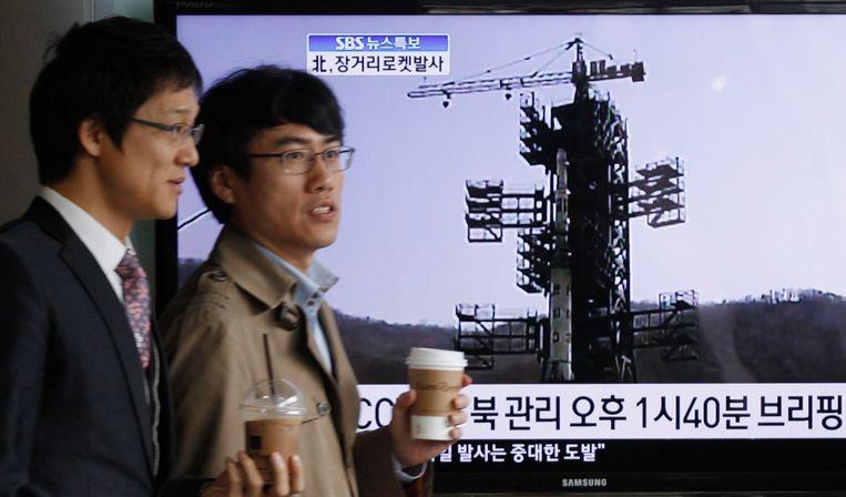 Zuid-Koreaanse mannen lopen langs een tv-scherm met een reportage over de Noord-Koreaanse raketlancering. Beeld REUTERS