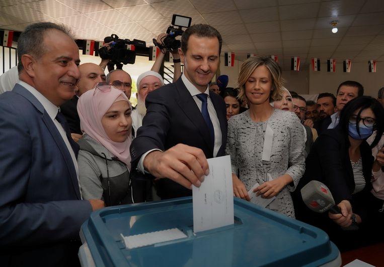 De Syrische president al Assad brengt zijn stem uit, met rechts naast hem zijn vrouw Asma al Assad. Beeld via REUTERS
