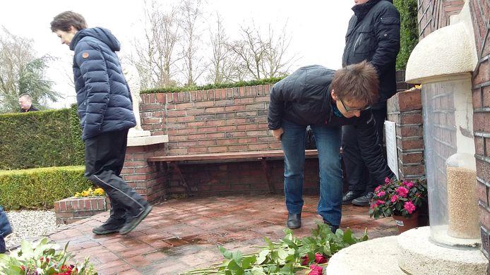 Mensen leggen bloemen bij het monument aan het Rademakersbroek. Rechts de pot met graan.