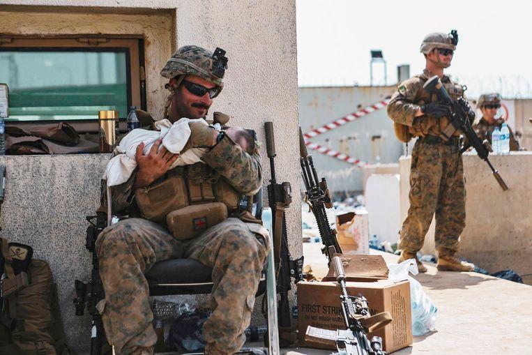 Een Amerikaanse marinier met een baby op het vliegveld in Kabul.  Beeld Brunopress