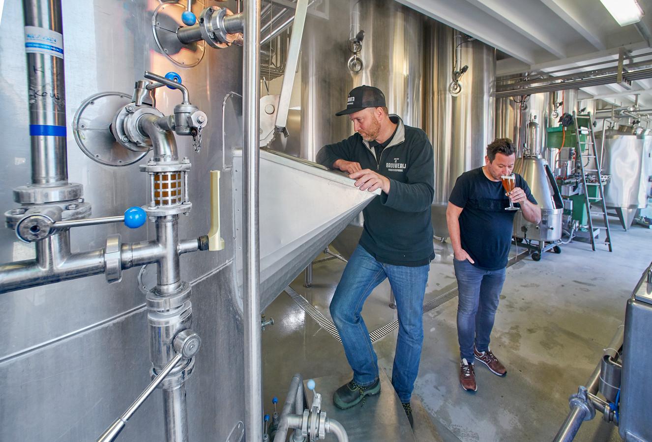 Brouwmeester Frans Schamp tuurt in de brouwketel, terwijl Alwin Houwing een slok bier proeft. De twee brengen D'n Schele Os terug op de markt.