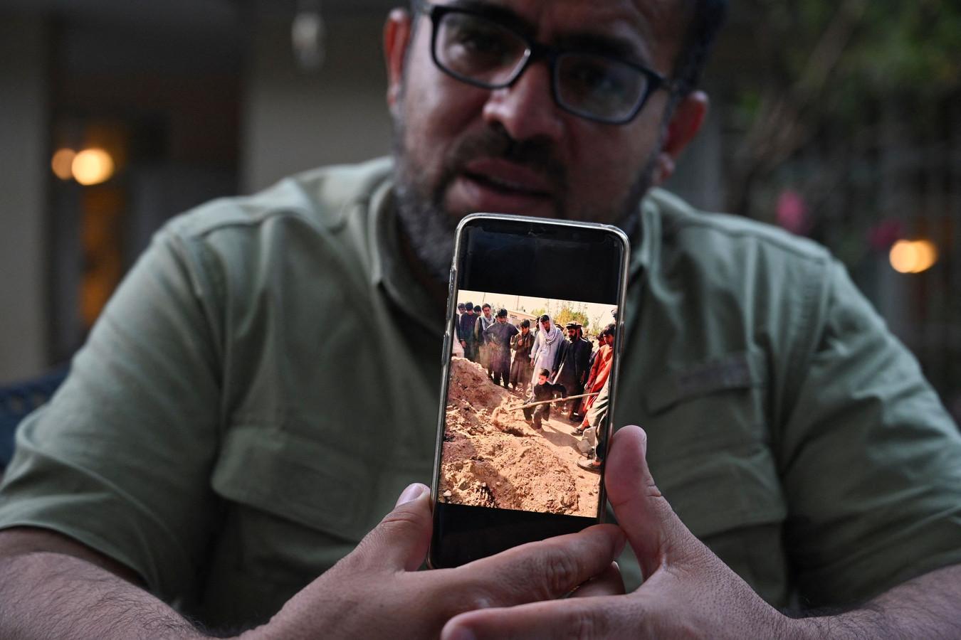 Foto van 24 juni 2021. Ahmad Siyar Anwari, een vormalige Afghaanse tolk van het Franse leger, toont op zijn telefoon een beeld van de begrafenis van Abdul Basir. De 33-jarige Basir werkte in het verleden ook samen met het Franse leger in Afghanistan. Hij werd op 19 juni dood gevonden in de provincie Wardak en zou zijn doodgeschoten door militanten van de Taliban.