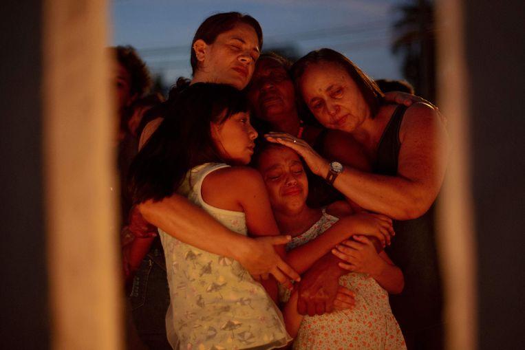 Mensen troosten elkaar tijdens de wake in Brumadinho. Beeld AFP