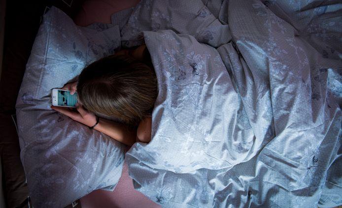 Een meisje chat terwijl ze in bed ligt.