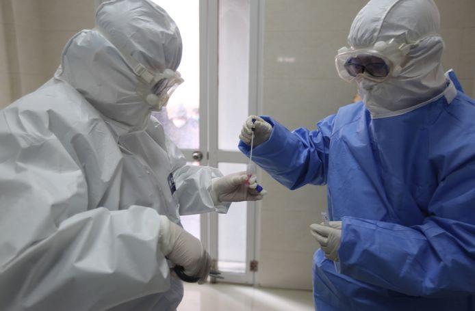 Een dokter in beschermkledij stopt een teststaafje waarmee hij een 'swab' maakte in de neus van een mogelijke patiënt in een buisje om naar een testlabo gebracht te worden.
