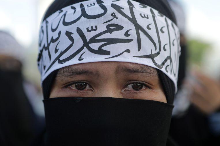 Een Indonesische betoger houdt het niet droog bij een demonstratie in Atjeh, tegen de onderdrukking van moslims in China.  Beeld EPA
