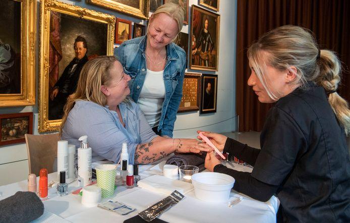 Een manicure en een leuk kleurtje op de nagels. Patricia Bousema (links) en haar zus Cindy laten zich een paar uurtjes verwennen op de eerste Wolkendag van de voedselbank.