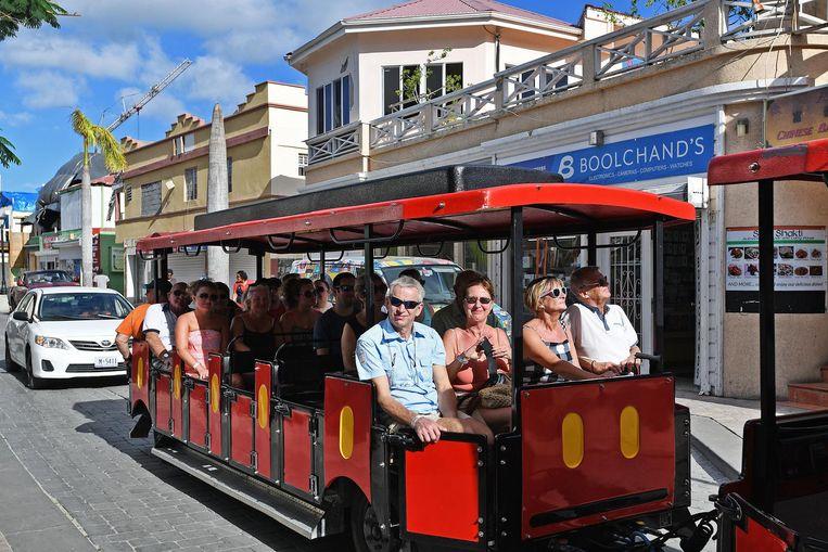 De eerste toeristentreintjes vol met toeristen van een bezoekend cruiseschip rijden door Front Street. Beeld Guus Dubbelman / de Volkskrant