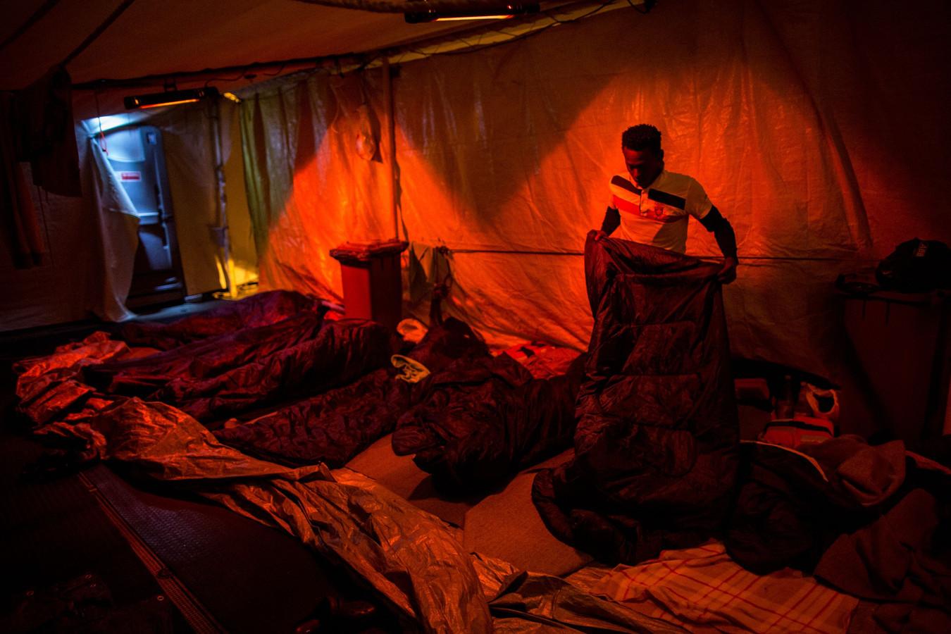 Een migrant maakt zijn slaapzak klaar om de nacht in door te brengen.