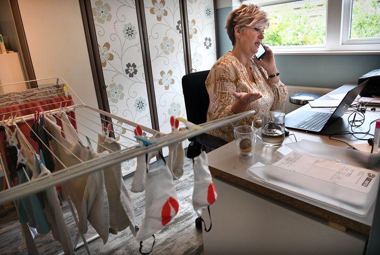 Kvk-medewerker Angèle Magré-de Monyé werkt vanuit haar washok en staat ondernemers met vragen over de steunmaatregelen te woord. Beeld Marcel van den Bergh