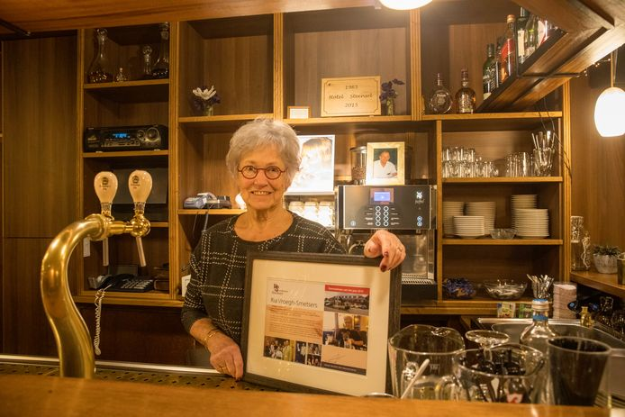 Ria Vroegh-Smetsers op de voor haar zo bekende stek achter de bar van Hotel Steensel met de oorkonde behorende bij de eretitel van Steenselnaar van het jaar.
