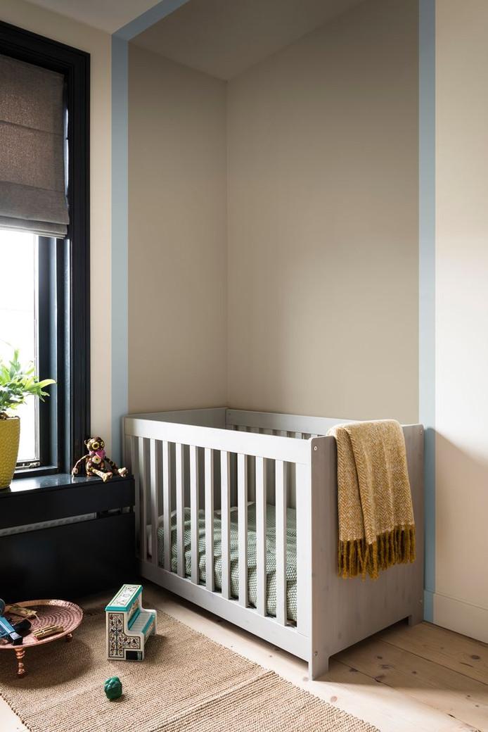 Bepaalde plekken in huis kun je accentueren door de zone te omlijsten met een bepaalde kleur. Het ledikant op deze foto krijgt zo alle aandacht.