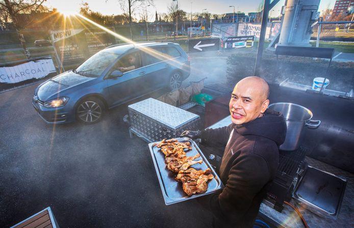 Melvin met kip op het rokerige parkeerterrein  van de Charcoal Drive Thru.