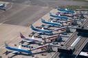 Vliegtuigen staan geparkeerd op Schiphol, omdat er minder gevlogen wordt.