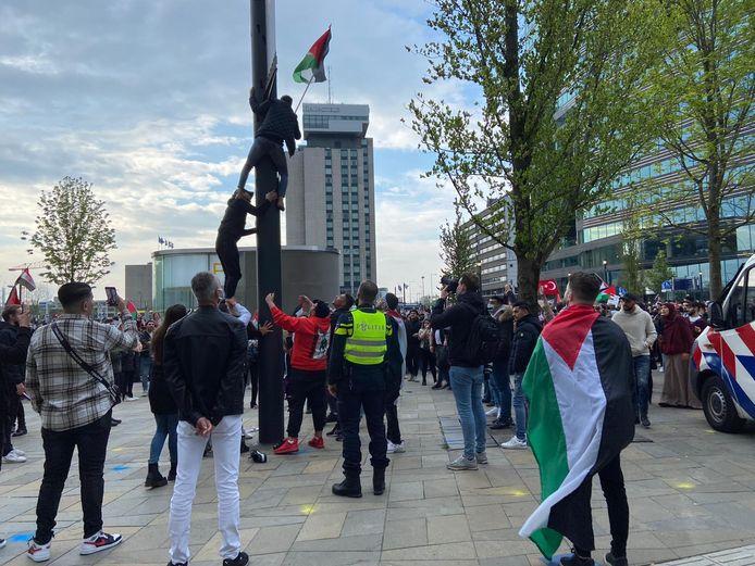 Twee demonstranten klimmen in een paal op het Jaarbeursplein