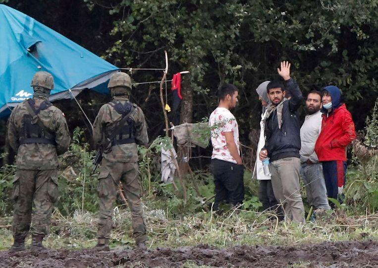 Poolse grenswachten bewaken een groep migranten die gestrand zijn in het gebied tussen Wit-Rusland en Polen. Beeld Reuters